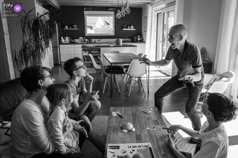 Savoie Documentary Family Photo | A daddy does a mime during a board game