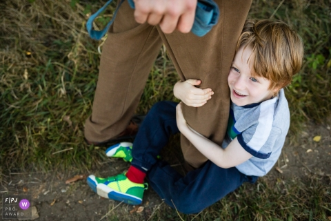 Cambridgeshire Family Photography of boy clinging to dad's leg on walk