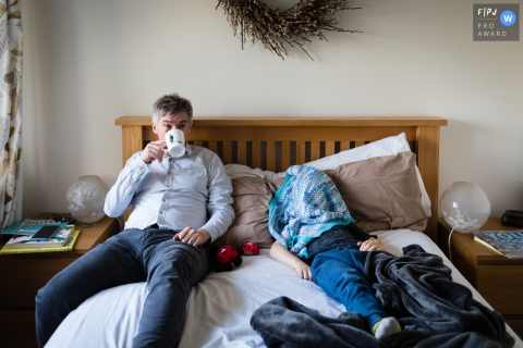 Cambridgeshire Documentary Family Photo of dad drinking tea in bed while boy hides under blanket