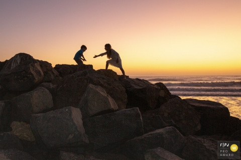 Ventura Documentary Family Photo | a silhouette image shows a girl reaching a hand out to help her brother navigate the rocks at the beach during sunset
