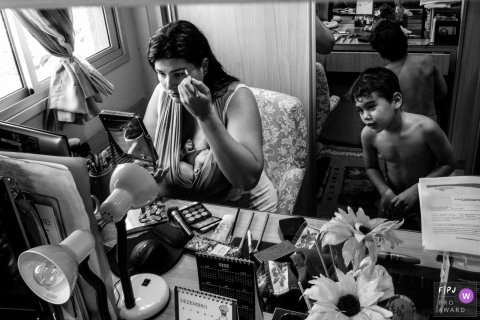 Cuiaba documentary family photo of a mother nursing, putting on makeup, with her older child nearby