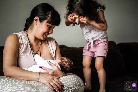 France Documentary Family Photographer | Young girl is taking photo with a toy of her little sister during the breastfeeding