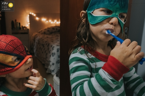 Sao Paulo Documentary Photographer | sisters dressed as super heroes before bed time, one brushing their teeth