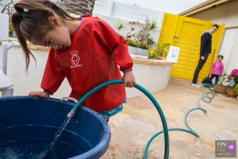 Los Angeles Documentary Family Photographer | A girl fills up a bucket with water while her dad and her sister awaits.