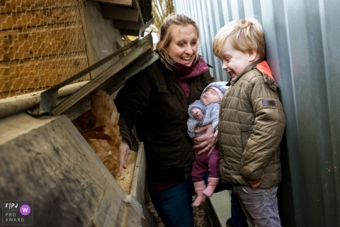 Netherlands Family Photographer | boy looking in wonder when finding a chicken egg in the nest