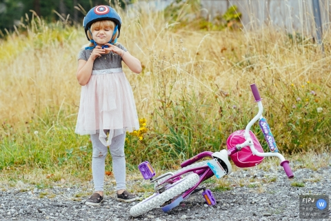 Washington Family Photography | girl strapping her helmet with her bike laying next to her