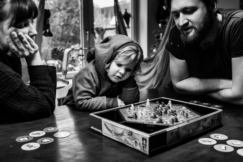 A family sitting at a table and playing games together. Polina Subbotina Fotografie