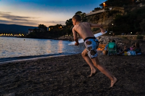 Boy surfing at sunset