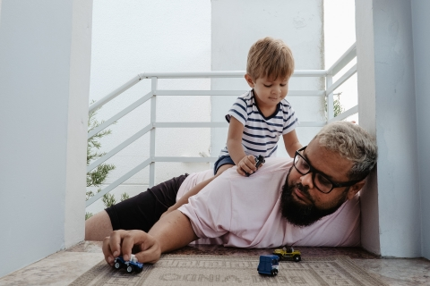 Father played with his son with toy car.