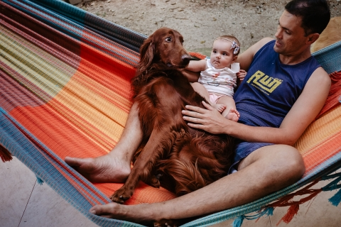 Father and daughter, in the hammock, with their dog.