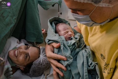 MG hospital documentary-style baby birth photo shoot of father holding his new baby at Maternidade Femina