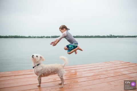 Sarasota Florida family photo of A young boy bravely jumping from the deck of his family lake house with his dog looking on