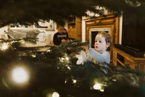 Little girl hanging a ball ball on the Christmas tree