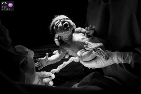 Maternidade Perinatal Barra hospital birth photo of a doctor showing everyone the baby just come out of mom's belly