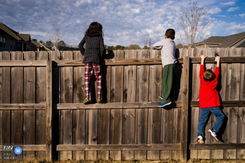 Atlanta Day in the Life Session of documentary family photography of children climbing a fence