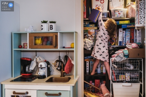 Antwerpen at home Day in the Life photography showing the Daughter trying to get her favorite toy by climbing in the closet