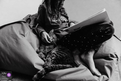 Wallonie Day in the Life documentary family photo of a child reading a book in a bean bag chair while petting a cat