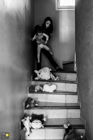 Day in the Life photography session at home inVar with some Cuddly toys, mom and child on the stairs in BW