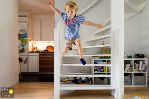 Day in the Life Zuid Holland documentary family photography session showing the Boy is jumping off the stairs