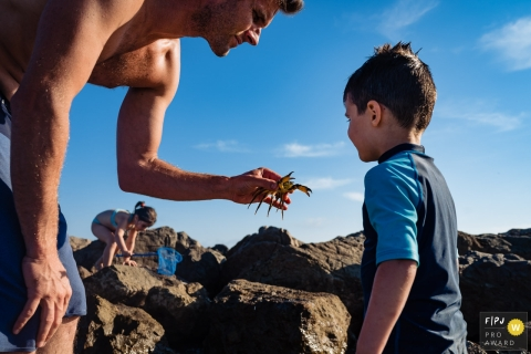 Perpignan Day in the Life Session of documentary family photography showing Dad is fearless as he handles a crab
