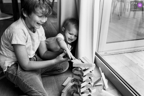 Day in the Life photography session at home inFlanders with kids playing by the window with wooden stacking block game