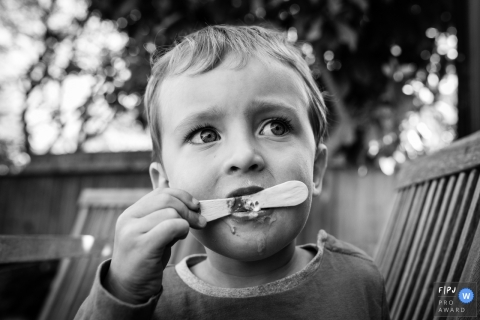 Day in the Life Cambridgeshire, England documentary family photography session showing a boy eats last of ice cream