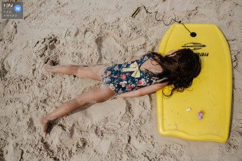 Florianopolis, Santa Catarina Day at the Beach documentary family photography of a girl lying on the beach sand, propped up under her surfboard