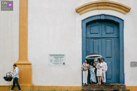 Florianopolis, Santa Catarina documentary family photography of a family waiting at the church door on a baptism day with a lot of rain