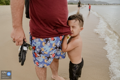 Arapongas, Parana Day in the Life documentary family photo of a beach scene with a young boy wiping his eyes on his dad's shirt