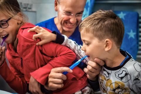 Dad brushing his kids teeth