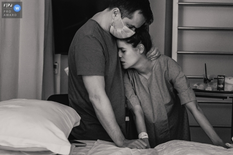 Moment-driven Hospital Albert Einsten birth photography of a husband comforting his wife during her labor