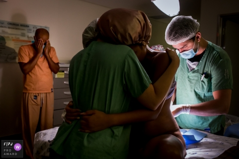 Moment driven Maternidade São Luis Itaim birth photojournalism image showing the father and the analgesia
