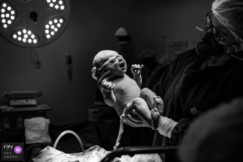 Moment-driven Maternidade Santa Helena birth photography showing the arrival of the baby in the delivery room