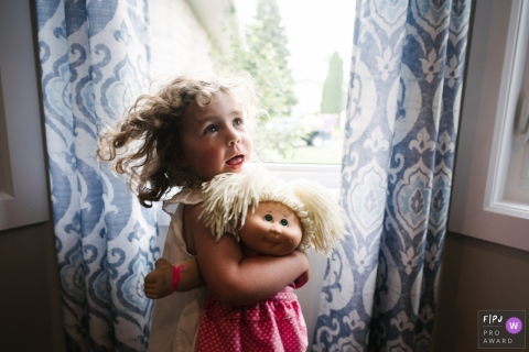 Moment driven Kingston family photojournalism image of a girl as she holds her favorite doll, who looks uncannily like her
