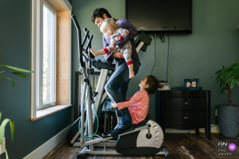 Moment-driven Kingston family photography capturing a dad juggles two kids who are constantly trying to climb the exercise equipment