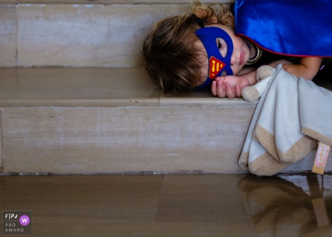 Moment driven Germany family photojournalism image showing a very tired superhero