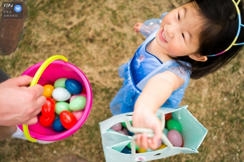 Moment-driven Atlanta family photography of a Girl showing off her Easter Egg collection