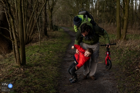 Moment driven Flevoland family photojournalism image of a toddler, father, and strider bike