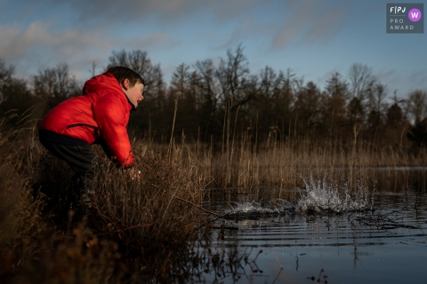 Moment-driven Flevoland family photography of a boy at a pond having some water fun