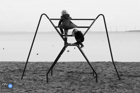 Moment-driven Amsterdam family photography of two children playing on a climbing frame