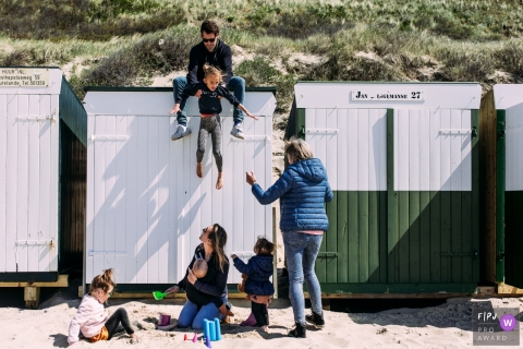 Moment driven Eindhoven family photojournalism image of a father dropping his child down off the roof of buildings at a beach