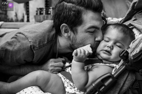 Moment-driven Belo Horizonte family photography when the father does not resist and kisses his baby with affection