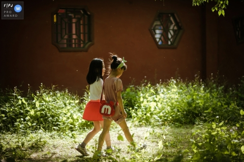 Moment driven Shanxi family photojournalism image of two good friends are walking and talking in beautiful forest sunshine