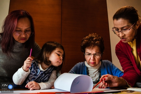 Moment-driven Istanbul family photography as women and child look through paperwork