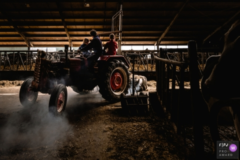 Moment driven Groningen family photojournalism image of kids helping dad feeding the cows on a tractor