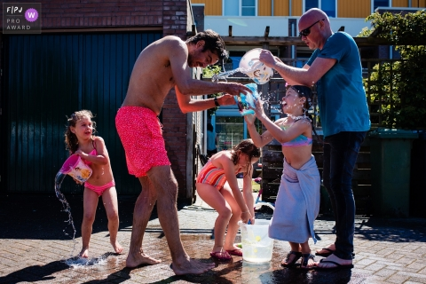 Moment driven Noord Brabant family photojournalism image of a family playing in the water on a hot day