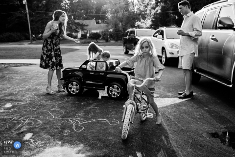 Moment-driven New Hampshire family photography of a Mom getting hit in the shins by toy car driven by two kids while dad looks on and big sister sits sadly on bike
