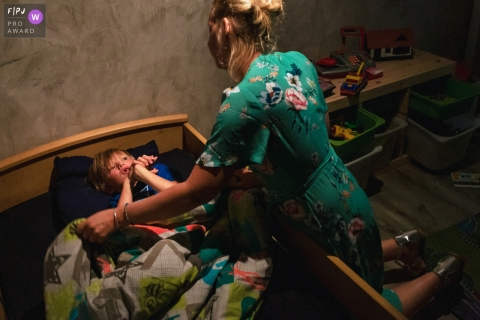 Moment-driven Paris family photography of a bedtime tuck in by mom