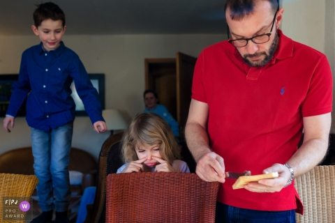 Moment driven Paris family photojournalism image of a father making toast for his waiting children