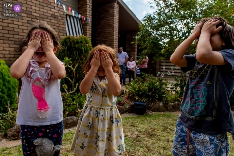 Moment driven Melbourne family photojournalism image of kids covering their eyes during a hide and seek session